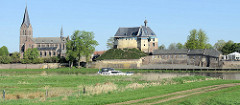 Blick über die Maas auf die Burgruine De Keverberg und die Dorfkirche von Kessel; ein Sportboot fährt flussabwärts.