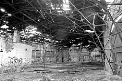 Innenansicht eines Ringschuppens / Lokschuppens; Licht schimmert durch die Löcher im Dach.