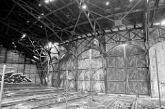 Einfahrten / Türen eines Ringschuppens der Eisenbahn; Schienenanlage mit Grube für Arbeiten unter der Lokomotive. Das Dach des Lokschuppens ist stark verfallen.