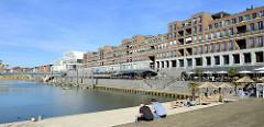 Promenade am Stadthafen von Venlo; Außengastronomie am Wasser, eine Terrassen mit Treppen zum Hafen lädt zum Sitzen ein.