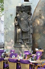 Steinskulptur - ein Bischof gibt den Segen über gedeckten Tischen mit violetten / lila Decken - Szene am Kakenberg in Maastricht.