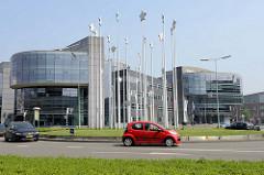 Moderne Bürogebäude  mit Glasfront - Kreisverkehr  vor dem Verwaltungsgebäude von Limburg in Maastricht - die europäischen Sterne sind auf langen Stangen in der Platzmitte aufgespießt / Europa Denkmal zur Einführung der Eurowährung in der EU.