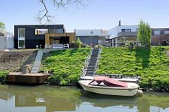 Moderne Wohnhäuser / Neubauten am Fluss Rur in Roermond; am Bootsanleger liegt eine Sloep / Tuckerboot.