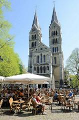 Ehemalige Zisterzienser-Klosterkirche Onze-Lieve-Vrouwe-Munsterkerk / Münsterkirche in Roermond; auf dem Platz vor der Kirche / Munsterplein sitzen Touristen in einem Café in der Sonne.