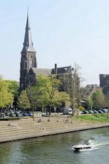 Blick von der Wilhelminabrug über die Maas zur katholischen        Sint Martinuskerk / St. Martinskirche; am Flussufer laden Terrassen zum Sitzen in der Sonne ein.