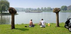 Picknick am Ufer der Maas in Maastricht - ein Fahrgastschiff / Ausflugsschiff fährt flussabwärts.