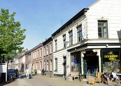 Einstöckige Wohnhäuser in der Heutzstraat von Venlo, Café mit Sesseln in der Sonne auf der Straße.