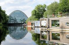 Moderne, neue Hausboote liegen am Ufer des Hochwasserbassins in Hamburg Hammerbrook; im Hintergrund das Bürogebäude Berliner Bogen.