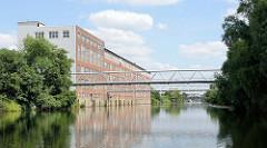 Gewerbegebäude / Lagerhäuser am Ufer des Billbrookkanals in Hamburg Billbrook - im Hintergrund die Wöhlersbrücke.