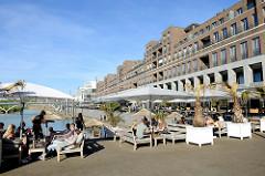 Promenade am Stadthafen von Venlo, lang gezogene mehrstöckige Wohnhäuser - Gastronomie mit Holzbänken und Sonnenschirmen am Wasser.