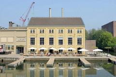 Blick vom Maasboulevard über das Bassin in Maastricht; ein altes Hafengebäude ist das restauriert und wird als Restaurant und Kino  genutzt.