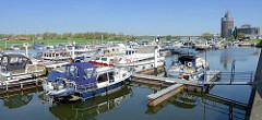 Marina / Stadthafen von Roermond an der Maas - Sportboote liegen am Steg, im Hintergrund die Autobrücke über den Fluss und der Natalini Turm, 63 m hoher Büroturm. / Bürokomplex, Entwurf von den Architekten Adolfo Natalini  in Zusammenarbeit mit d