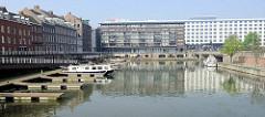 Altes Hafenbecken  / Bassin am Maasboulevard in Maastricht. Bootsstege und Motorboote liegen in der Marina - im Hintergrund neugebaute Wohnhäuser mit Balkon und die Fabrikgebäude der ehemaligen  Keramikfabrik Sphinx.