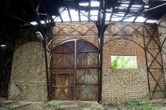 Türen - teilweise zugemauert - eines Ringschuppens der Eisenbahn; das Dach des Lokschuppens ist stark verfallen.