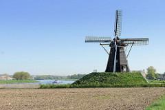 Windmühle am Ufer der Maas auf dem Weg nach Roermond - ein Binnenschiff fährt flussabwärts.