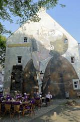 Fassadenbild / Fassadenmalerei an einer Hauswand am Kakenberg in Maastricht - Restaurant mit Tischen unter dem Baum.
