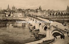 Historisches Panorama der Stadt Maastricht in den Niederlanden; Kirchtürme über den Dächern der Stadt; und Passanten schlendern über die Steinbrücke.