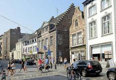 Wohnhäuser mit Geschäften im Erdgeschoss - unterschiedliche Architekturformen in der Grote Gracht von Maastricht; Radfahrerinnen fahren auf der Straße, Fußgänger überqueren einen Fußgängerüberweg.