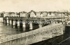 Historische Ansicht der Brücke über die Maas bei Maastricht. Eine hohe Kaimauer schützt die Wohnhäuser vor Hochwasser, rechts Fabrikschornsteine / Schlote von Fabrikanlagen. Im Vordergrund führt eine Rampe zur Straße und Brücke.