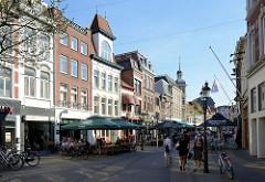 Fußgängerzone, Einkaufsstraße Parade in Venlo. Restaurants und Cafés haben ihre Tische mit Sonnenschirmen auf die Straße gestellt.