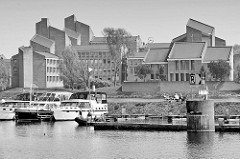 Sportboote / Motorboote liegen in einer Marina eines alten Hafenbecken an der Maas bei Maastricht; im Hintergrund das Gouvernement der Stadt - dort wurde 1992 der Vertrag von Maastricht unterzeichnet.