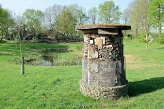 Biotop an der Maas auf dem Weg nach Roermond; Teich mit Schilf großes zylindrisches Insektenhotel mit den unterschiedlichsten Unterschlupfmöglichkeiten.