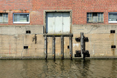 Gewerbegebäude mit Ladeluke am Billbrookkanal in Hamburg Billbrook; Holzpfähle / Holzdalben schützen die Hauswand beim Anlegen der Frachtschiffe / Binnenschiffe.