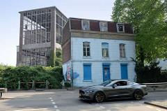 Alleinstehendes kleines, verlassenes Wohnhaus im Hafengebiet von Maastricht dahinter ein verlassenes Werftgebäude am Biesenwal iin Maastricht.