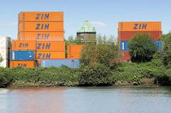 Blick über den Schmidtkanal in Hamburg Wilhelmsburg zu einem Containerlager am Kanalufer - dazwischen die Kupferkuppel vom Wilhelmsburger Wasserturm.