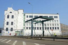 Klappbrücke  über die Schleuse zum Bassin in Maastricht; weiß gestrichenes Lagergebäude / Industriearchitektur.