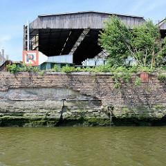 Alter Hafenkai im Hamburger Hafen; die Kaianlage verfällt, Wildkraut / Unkraut wuchert aus den Mauerritzen. Schild für die Schifffahrt, Parken / Anlegen verboten.