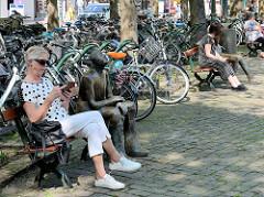 Munsterplein / Platz vor der Munsterkerk / Münsterkirche in Roermond; dicht beieinander geparkte Fahrräder - Sitzbänke mit Bronzeskulpturen.