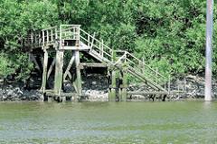 Verlassene Holztreppe im Hafen Hamburgs / Hafenbecken Moldauhafen;  der Zugang ist mit Gebüsch zugewachsen, die Holzkonstruktion ist bei Niedrigwasser freigelegt und gut zu erkennen.