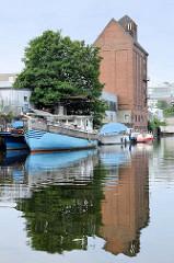 Motorboote liegen am Ufer des Mittekanals in Hamburg Hammerbrook; dahinter ein altes, allein stehendes Speichergebäude.