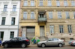 Als + neu; mehrstöckige Wohnhäuser in der Lindenstraße von Frankfurt/Oder; das linke ist frisch restauriert mit weißer Fassade, das rechte ist leer stehend und stark renovierungsbedürftig.