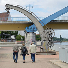 """Denkmalgeschützter Hafenkran an der Oderpromenade in Frankfurt; der Drehkran wurde um 1860 von der """"H. Gruson Maschinenfabrik Bockau bei Magdeburg"""" aus stark genieteten Eisenblechen hergestellt."""