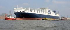 Der RoRo Frachter Atlantic Sun wird von Schleppern auf der Elbe vor Hamburg Steinwerder bugsiert - ein Fahrgastschiff einer Hafenrundfahrt passiert das grosse Frachtschiff.