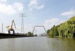 Blick vom Ende des Neuhöfer Kanals Richtung Süderelbe - eine Hochspannungsleitung verläuft am Kanalrand - eine Pipelinebrücke überquert den Kanal.