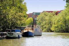 Containerlager und Boote am Ufer vom Jaffe David Kanal in Hamburg Wilhelmsburg - das Ufer ist mit Weiden und Sträuchern dicht bewachsen.