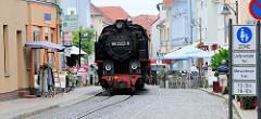 Die Bäderbahn Molli fährt durch die Fussgängerzone / Straße Molli in Bad Doberan. Der Zug wird von der Dampflok 992322-8 gezogen.