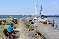 Hafenpromenade in Timmendorf auf der Insel Poel - Mecklenburg Vorpommern; Boote liegen am Steg - im Hintergrund die Hafenmole.