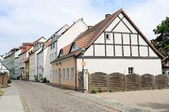 Im Vordergrund ein historisches Wohnhaus in der Fischerstraße von  Frankfurt/Oder, das Gebäude mit den Ochsenaugen Dachgauben und den Holzfensterluken steht unter Denkmalschutz.