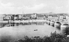 Altes Foto von der Stadtbrücke über die Oder bei Frankfurt; die 264 m lange Bogenbrücke wurde 1895 erbaut. Auf der Brücke fahren Pferde-Wagen - auf dem Fluss zwei Holzboote mit Anglern. Am Ufer stehen Wohn- und Speichergebäude.