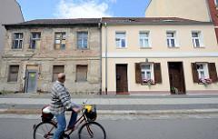 Neu + alt, Wohnhäuser in der Ziegelstraße von Frankfurt/Oder; eines der Gebäude ist aufwendig restauriert mit Holzluken und Geranien vor dem Fenster, das andere ist verfallen mit abgebröckeltem Putz und vernagelten Fenstern.