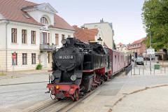 Die Bäderbahn Molli mit der Dampflok  992322-8 am Alexandrinenplatz in Bad Doberan - im Hintergrund das Haus Gottesfrieden des Stadtarchitekten Carl Theodor Sverin, das im klassizistischen Baustil 1824 errichtet wurde.