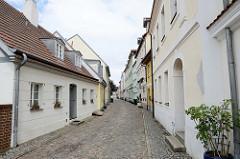 Historische Architektur in der Fischerstraße von Frankfurt/Oder - schmale Gasse mit Kopfsteinpflaster, die vorderen Gebäude links und rechts stehen unter Denkmalschutz.