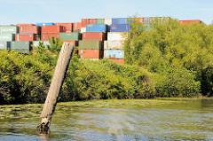 Containerlager am Ufer vom Jaffe David Kanal in Hamburg Wilhelmsburg - ein halb abgebrochener Dalben steht im Kanalwasser.