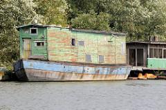 Altes Hausboot am Spandauer Ufer im Hamburger Spreehafen; die Farbe blättert am Holzaufbau des Arbeitsbootes ab.