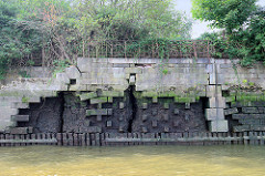Kaimauer am Moldauhafen im Kleinen Grasbook; das Niedrigwasser legt das Holzfundament und Reste einer Ziegelmauer frei - in breite Risse kann Wasser eindringen. Lks. eine Treppe zum Wasser - oben ein altes Eisengeländer.