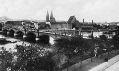 Altes Foto von der Stadtbrücke über die Oder bei Frankfurt; die 264 m lange Bogenbrücke wurde 1895 erbaut. Im Hintergrund Kaianlagen am Fluss sowie die Doppeltürme der Friedenskirche und das hohe Dach vom Franziskaner Kloster-Kirche.